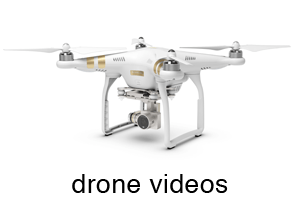 "A white quad-copter drone, with a mounted camera underneath. Reads ""Drone videos"""