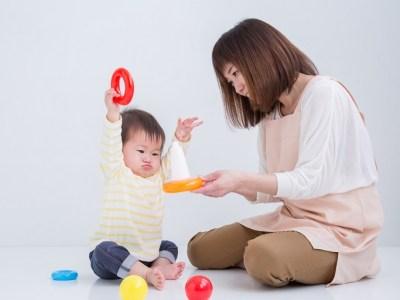 子どもと遊ぶエプロン姿の女性