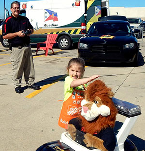 Catherine O'Neill of Arabi pets the head of Daren the Lion, mascot of the D.A.R.E. drug resistance education program last October at Home Depot Kids Safety Day. In the background operating the remote control car is Sgt. Darrin Miller of the D.A.R.E. program.