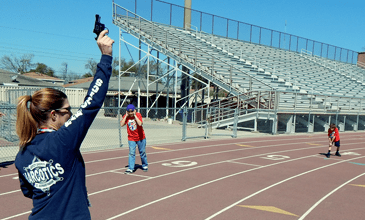 Sgt. Jessica Gernados, helping with events, fires a starter's pistol to begin a race.