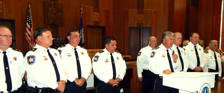 The sheriff speaks, surrounded by ranking officers of the department.