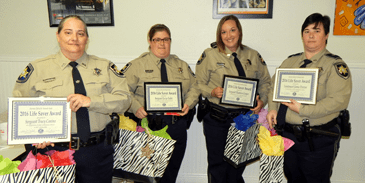 Four representatives of the Communications Division hold their Life-Saver Award certificates and gifts they received. From left are Sgt. Tracy Canino, Sgt. Lacye Lulei, Sgt. Shannon Cooper and Lt. Jamie Penton.