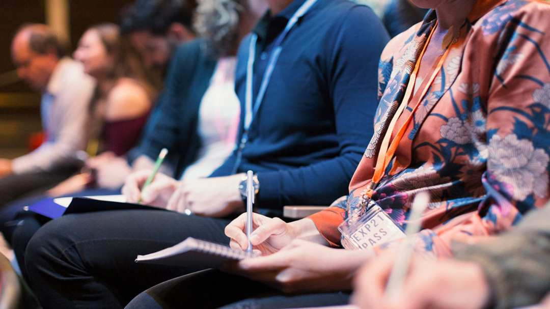 Women taking notes at a conference