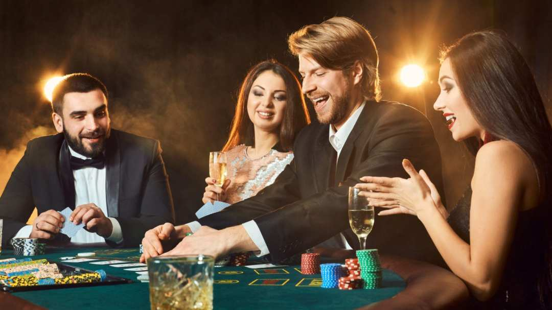 Four adults in dressy clothing playing cards at a table