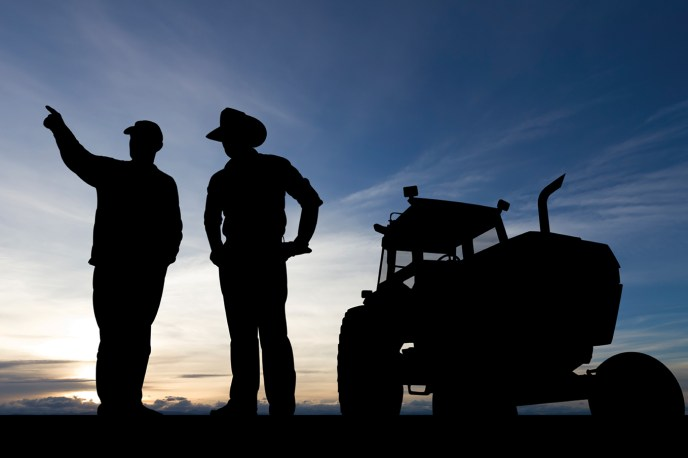 Silhouettes of two farmers looking over fields with tractor behind them
