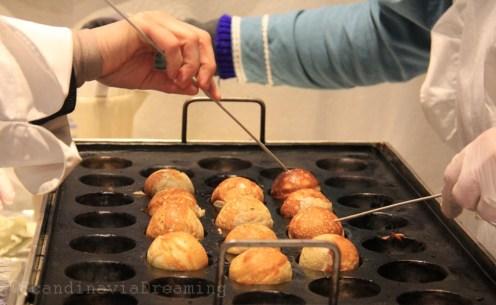 Confection artisanale des aebleskiver au marché de Noël d'Andersen