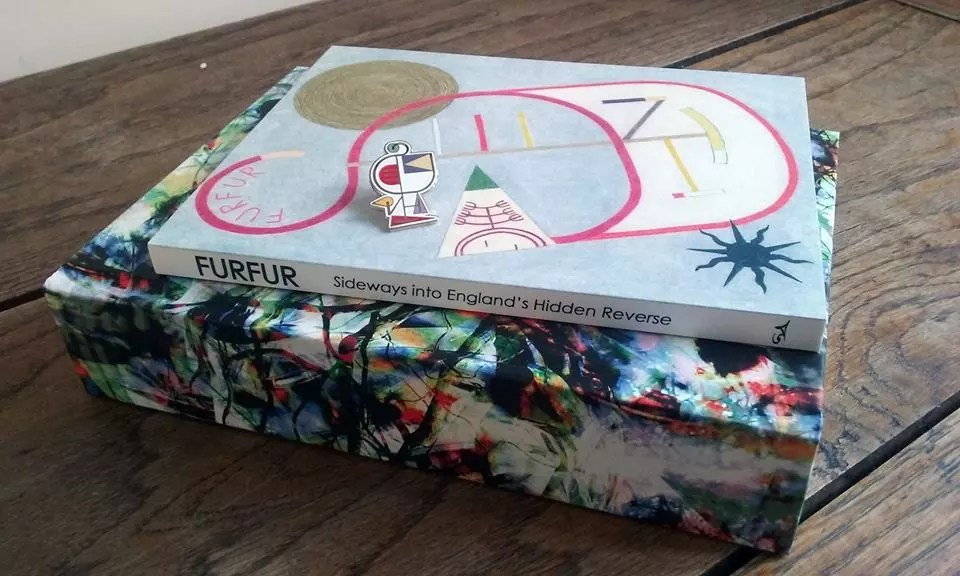 Two books on top of each other sitting on a desk. Colourful abstract swirling images over both of them
