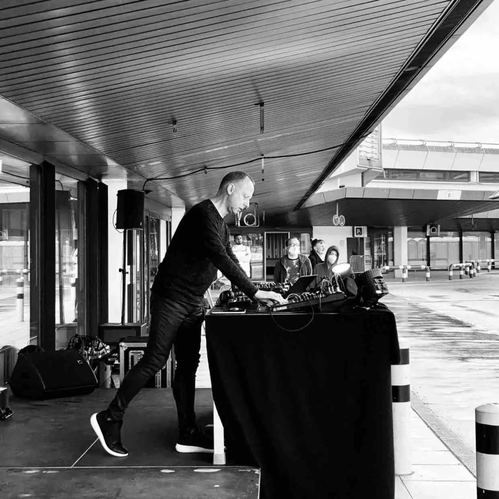 Black and white image of Robin Rimbaud, an older white man, in tight black coated jeans, shoes with a white layer at the bottom, black jumper. He's leaning over a large table with a bank of electronic equipment performing outdoors at Tegel Airport in Berlin