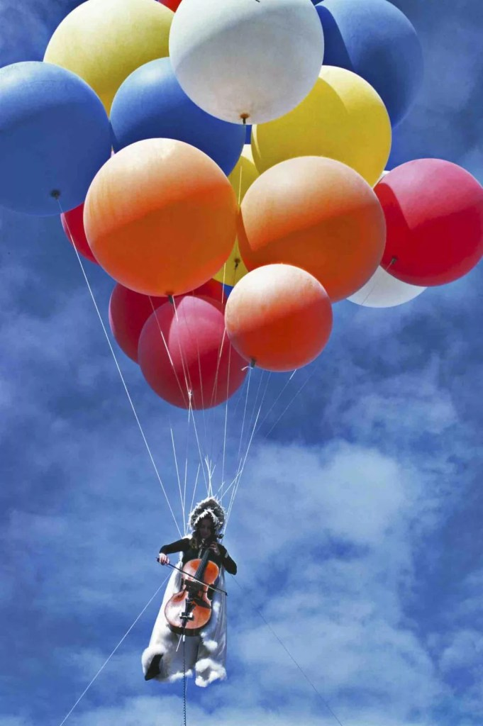Very colourful image of a woman playing the cello floating in the sky, held up by about a dozen large colourful balloons, red, blue, orange, yellow, white. The sky behind is a bright blue with light white clouds