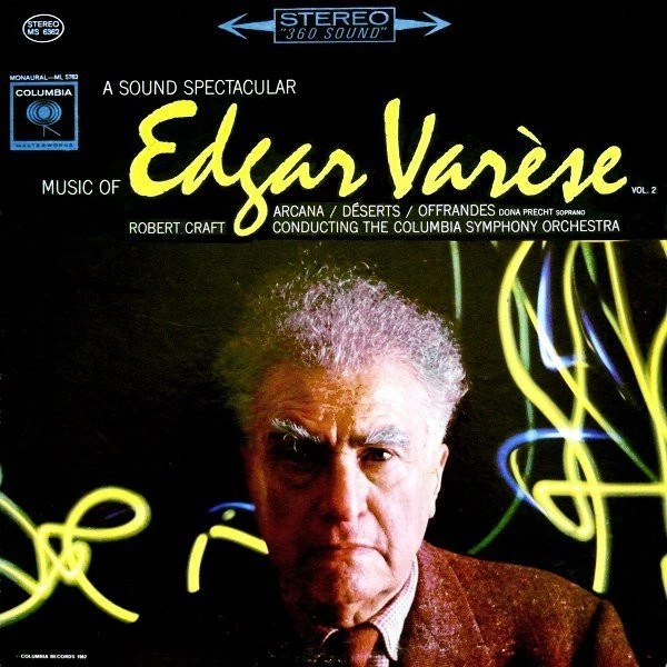 A very colourful and dramatic vinyl LP sleeve, with handwritten text Edgard Varèse in yellow across a photograph of an elderly white man in a smart brown suit staring directly at the camera