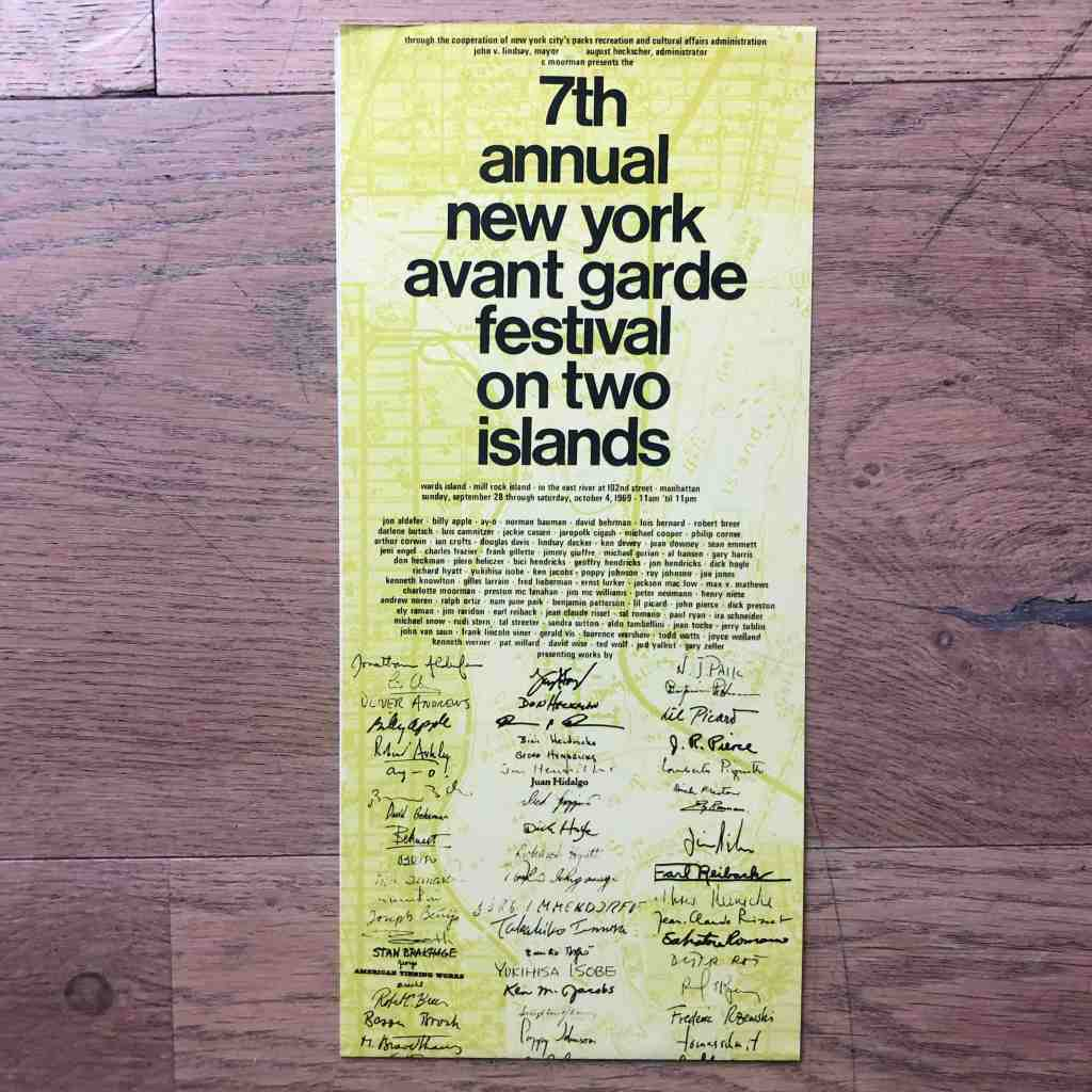 A colour image of a yellow and green tinted piece of paper on a wooden floor. The paper is filled in tiny script with handwriting and printed text listing the 7th annual new york avant garden festival on two islands