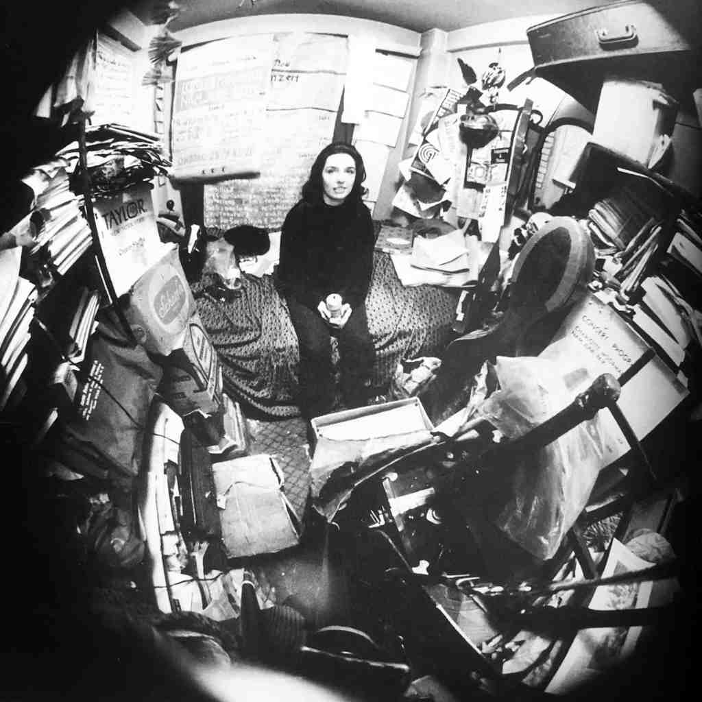 Black and white image of a woman seated on a bed, dressed all in black, surrounded by furnishings and her belongings on every surface. The walls are covered in papers, objects lie on every shelf. The photograph uses a fish eye lens so the focus is directly on the main woman