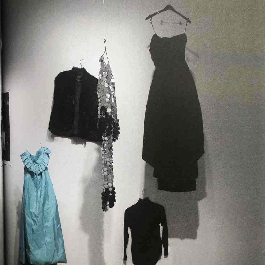 Several dresses hang up on a white wall, suspended by wires. Black dresses and a blue dress hang with a lot of space between them