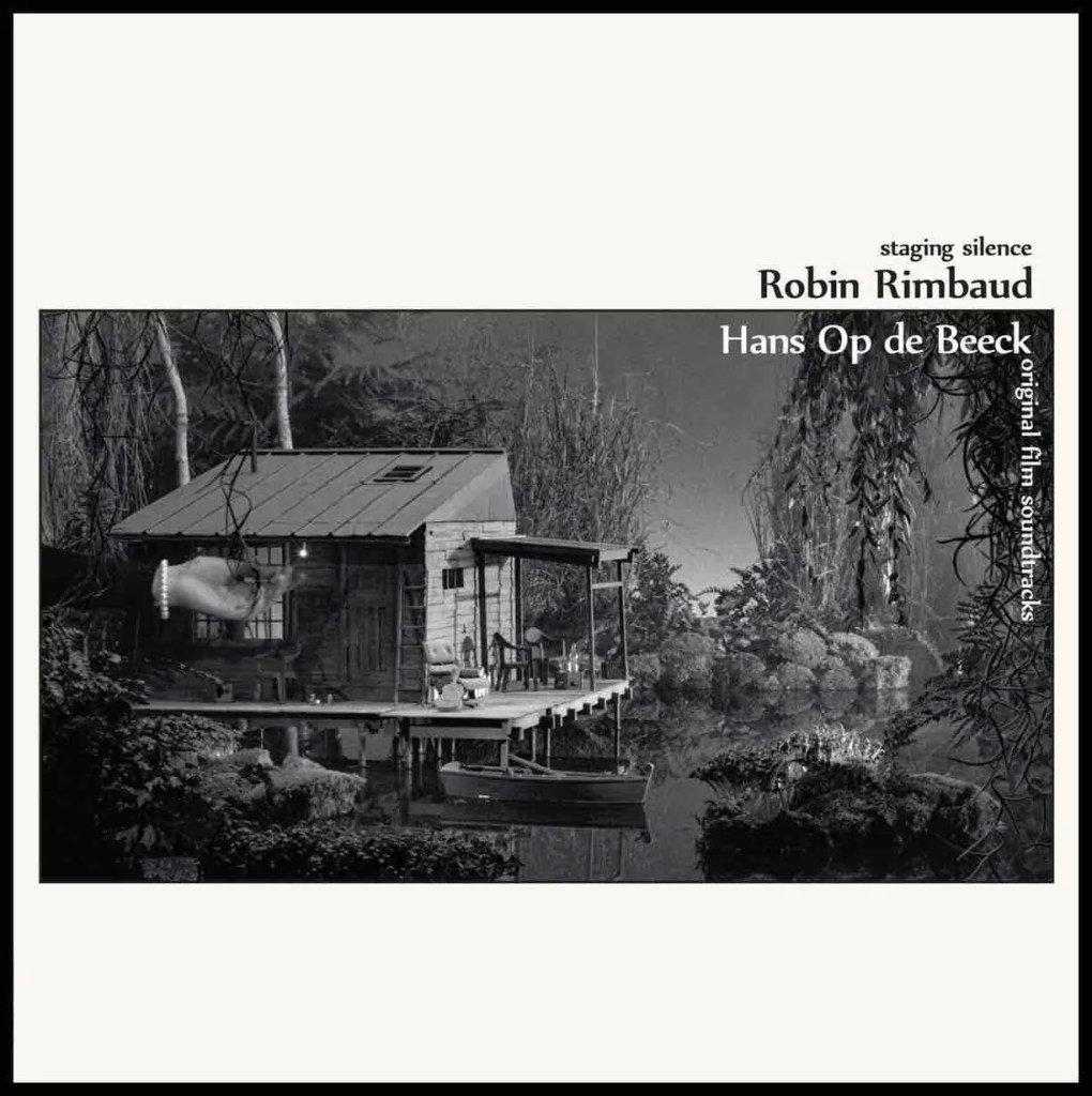 Black and white photograph of an album cover. A jungle image with a little wooden hut, sitting on the water front is shown to be fake with a human hand coming in at the left side adjusting the image. A text reads Staging Silence Robin Rimbaud Hans Op de Beeck on the artwork