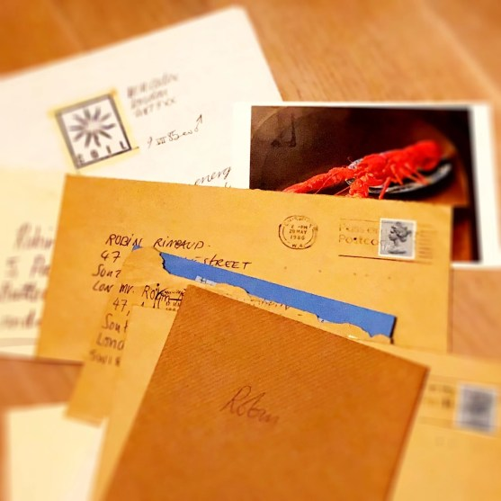 Collection of letters and postcards on a desk, with handwriting on each. Not possible to read the texts