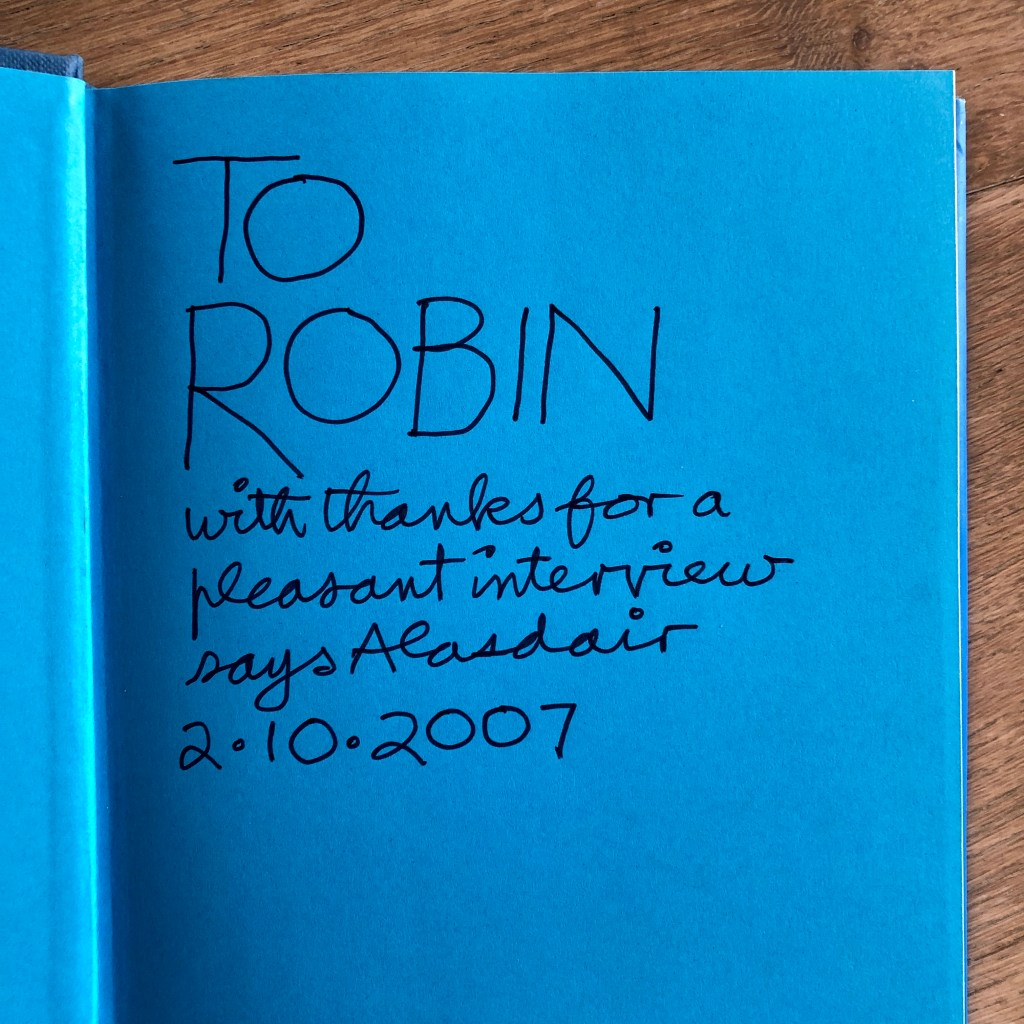 The inside cover of a book, with black ink on blue paper, with handwritten text that reads 'To Robin with thanks for a pleasant interview says Alasdair 2.10.2007