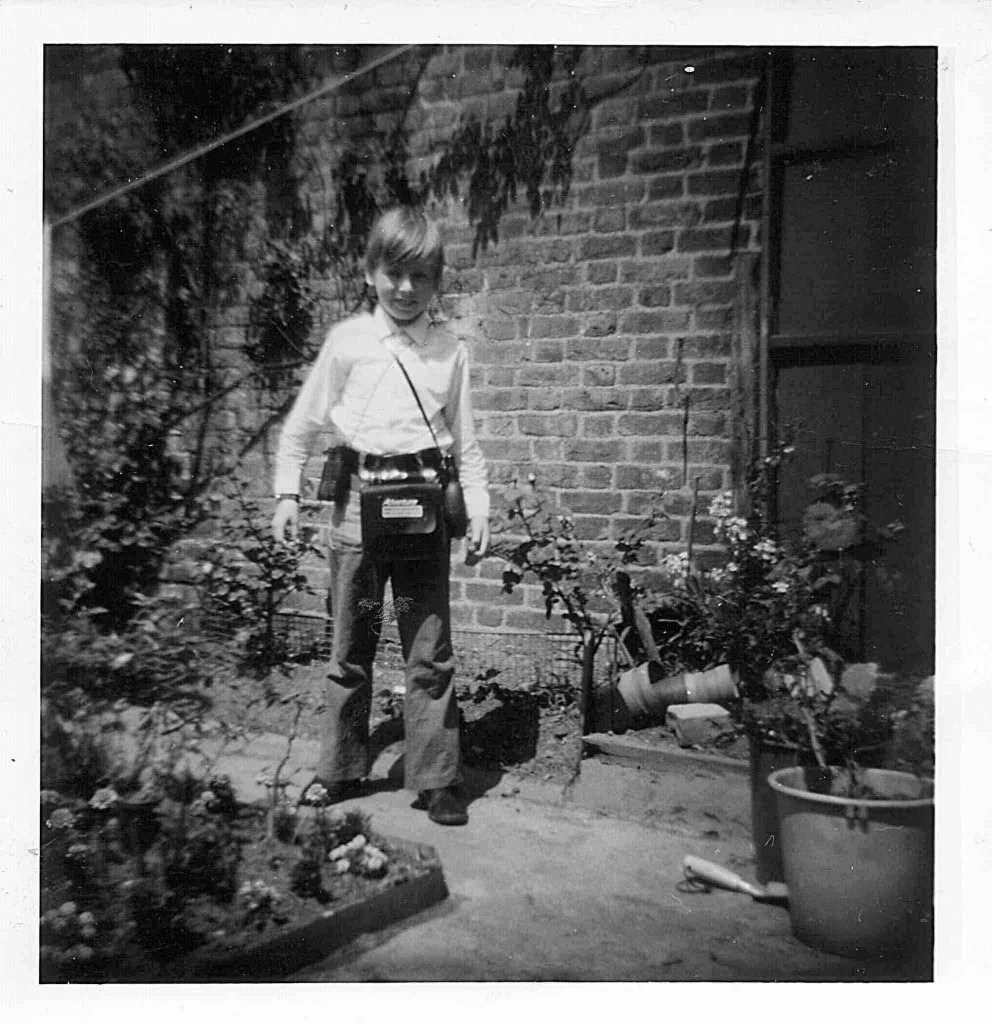 Black and white photograph from 1970 of a young boy aged around 8 standing in the garden, wearing a white shirt and slightly flared jeans. He's got blonde hair over his forehead and wears binoculars and other items around his neck