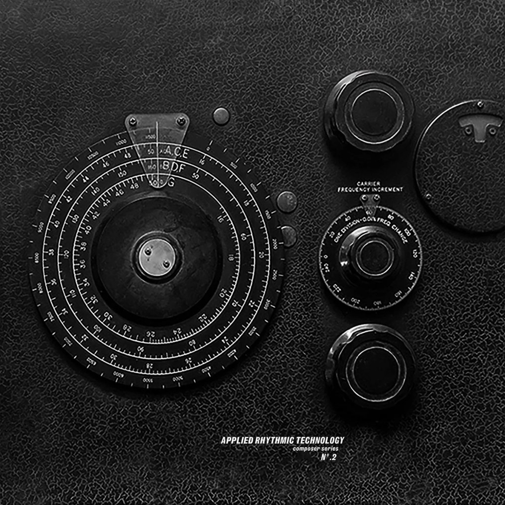 Bold black and white image of electronic dials on a black background. Some kind of musical modular synth, almost scientific