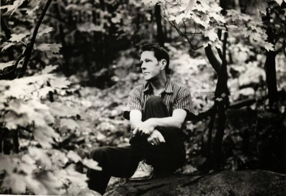 Black and white photograph of a man, the American composer John Cage, sitting in a forest, casually dressed, staring thoughtfully into the distance