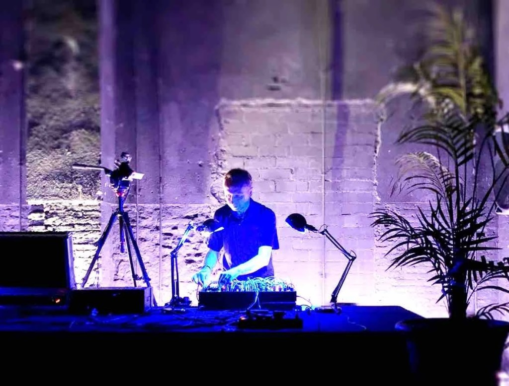 Man stands behind a bank of synthesisers, with a concrete wall behind him. Blue light filters the Image. Cameras and a palm tree stand either side of him during a live musical performance