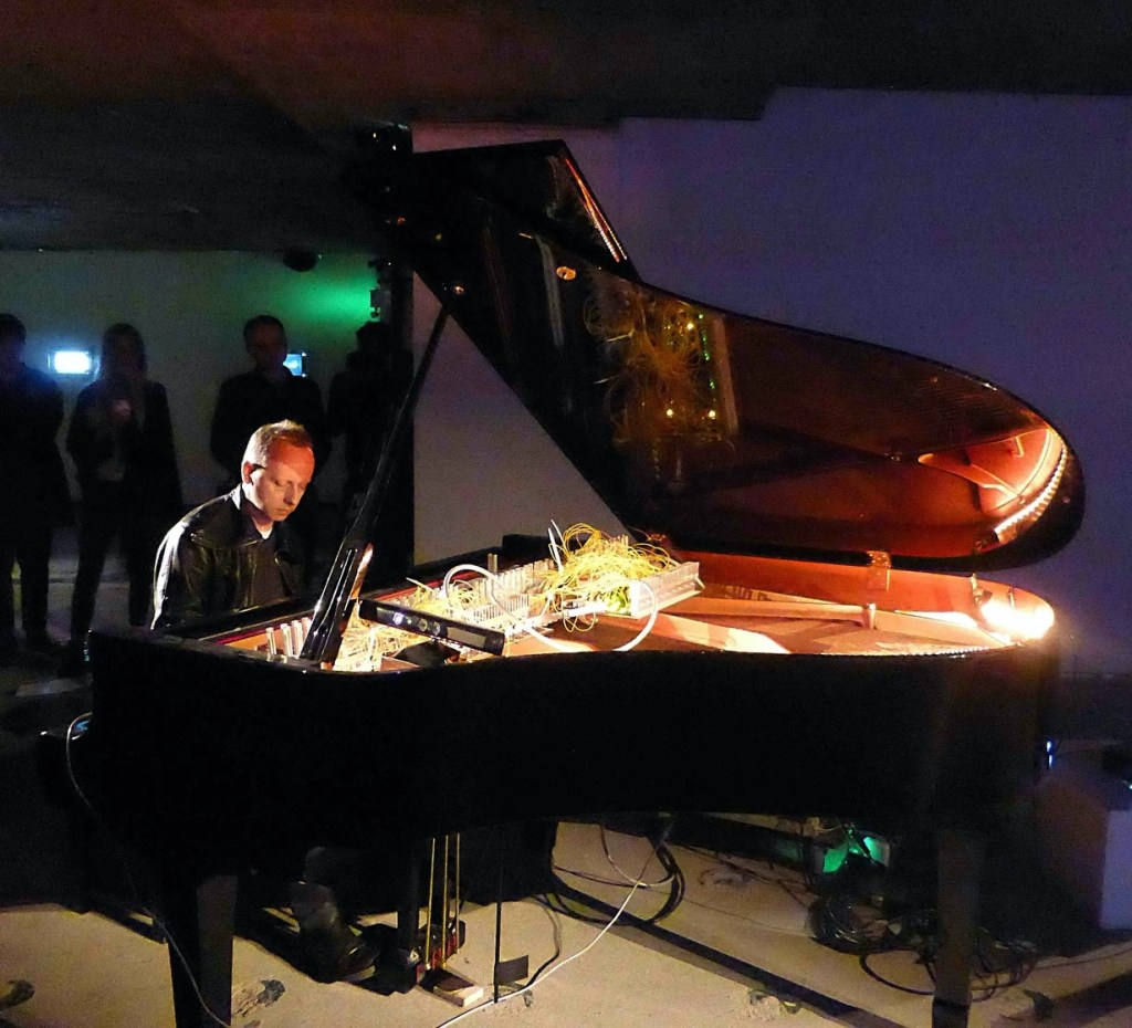 Photograph of a man in leather jacket sitting playing the piano. The piano has all kinds of wires and cables inside it, There are people standing in the room behind the pianist, in the dark