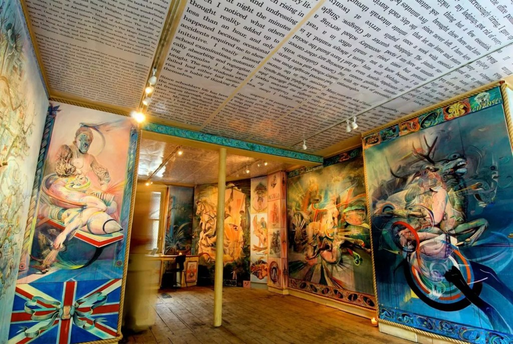 Very brightly coloured paintings in a small gallery space, with black and white printed text all across the ceiling. The floor is wooden and the only place which does not display artworks