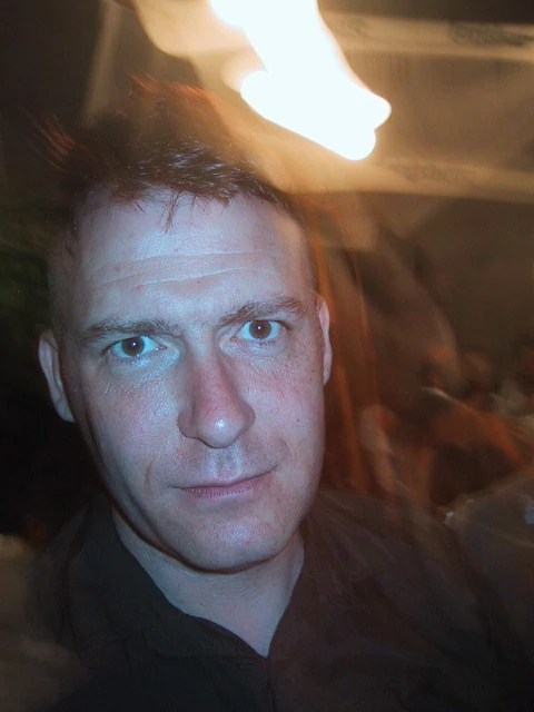 Photograph of a man, a close up portrait, aged around 35, white, fresh, slim looking, with light exploding above him as if it is leaking in