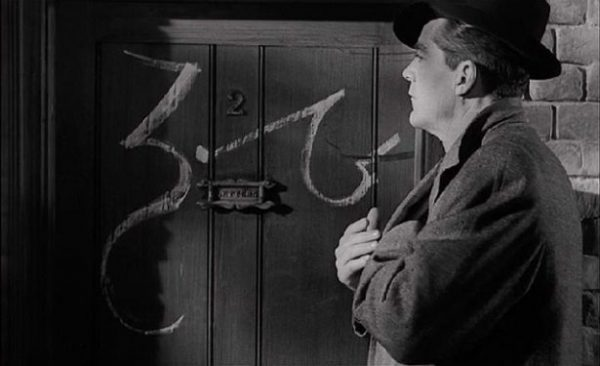 Dana Andrews muses over the strange script on the door in Curse of the Demon (1956)
