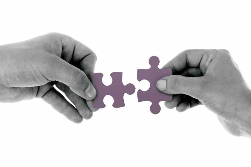 two puzzle pieces being connected together by hands