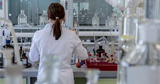 Female scientist in a while lab coat busy at work, we are looking at her from behind through some glass bottles