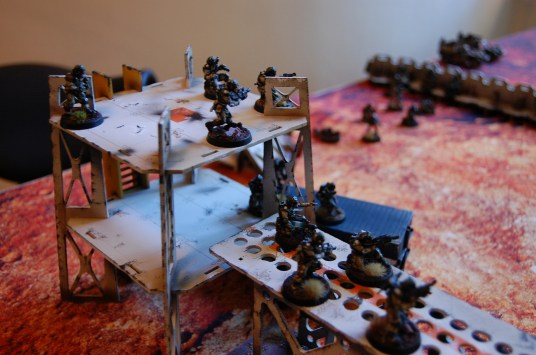 Infantry squads scale the catwalks linking two of the guard towers. Four units are deployed in tactical reserves to utilize the Elysian Aerial drop deployment. The warlord, the veteran squad, a command squad, and the Drop sentinels make themselves ready for planetfall...