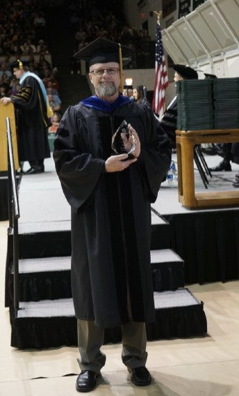 2018 Instructor of Year, as selected by SCCC students, Dr. Russ Reglin, leaves the stage with his award at the 47th annual commencement ceremonies.