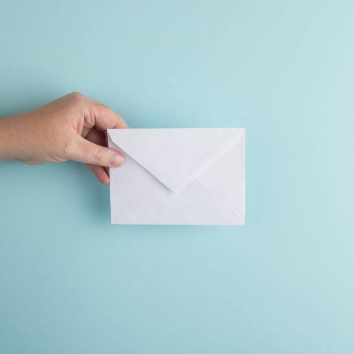 hand holding white envelope