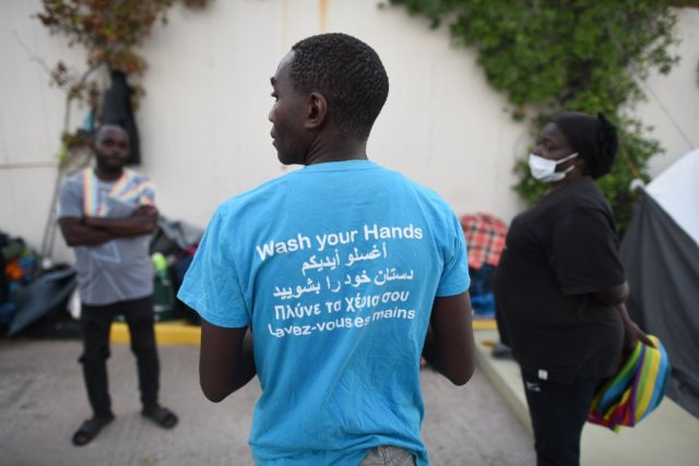 Dadi Mukendi a Congolese asylum seeker shows the back of his t-shirt instructing people to regularly wash their hands