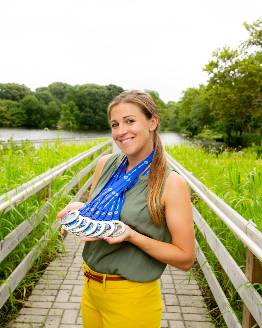Woman holding medals from marathons standing on a trail