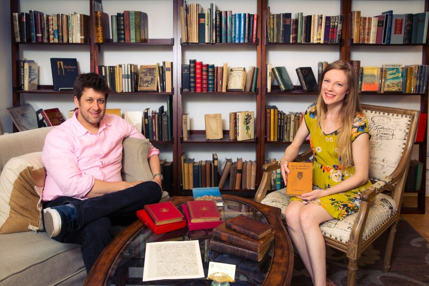 The owners of B and B Rare Books hold a copy of a rare book and sit on couches in their gallery.