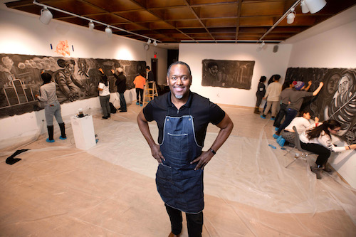 Artist Steve Prince standing in the Kinetic Gallery with students drawing on the murals.