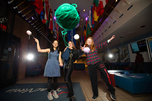 Three members of the Stitches knitting and crochet club throw yarn at the camera from the student union