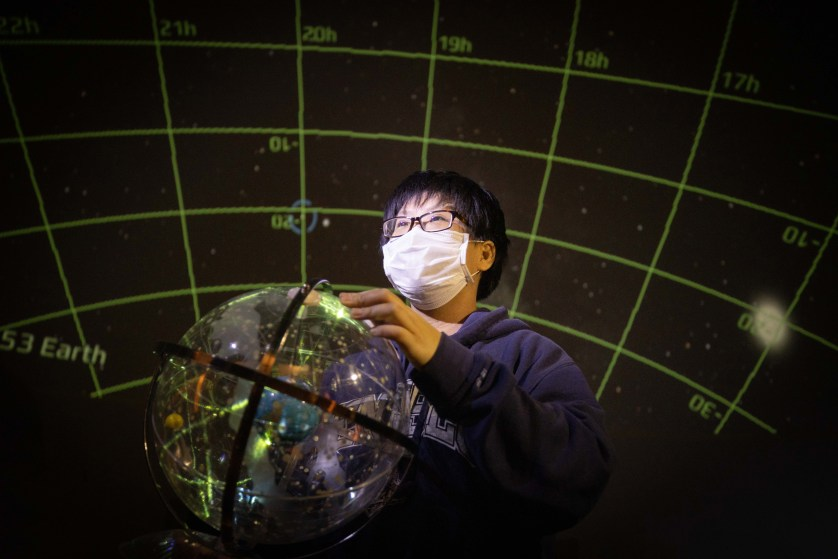 Nami Nishimura '21 with a globe and stars reflected in it.