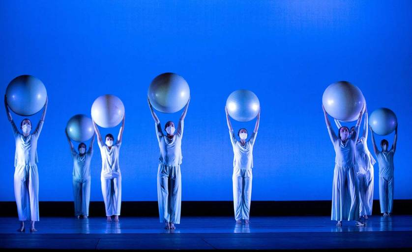 Geneseo Dance Ensemble members hold balls above their head in a piece.