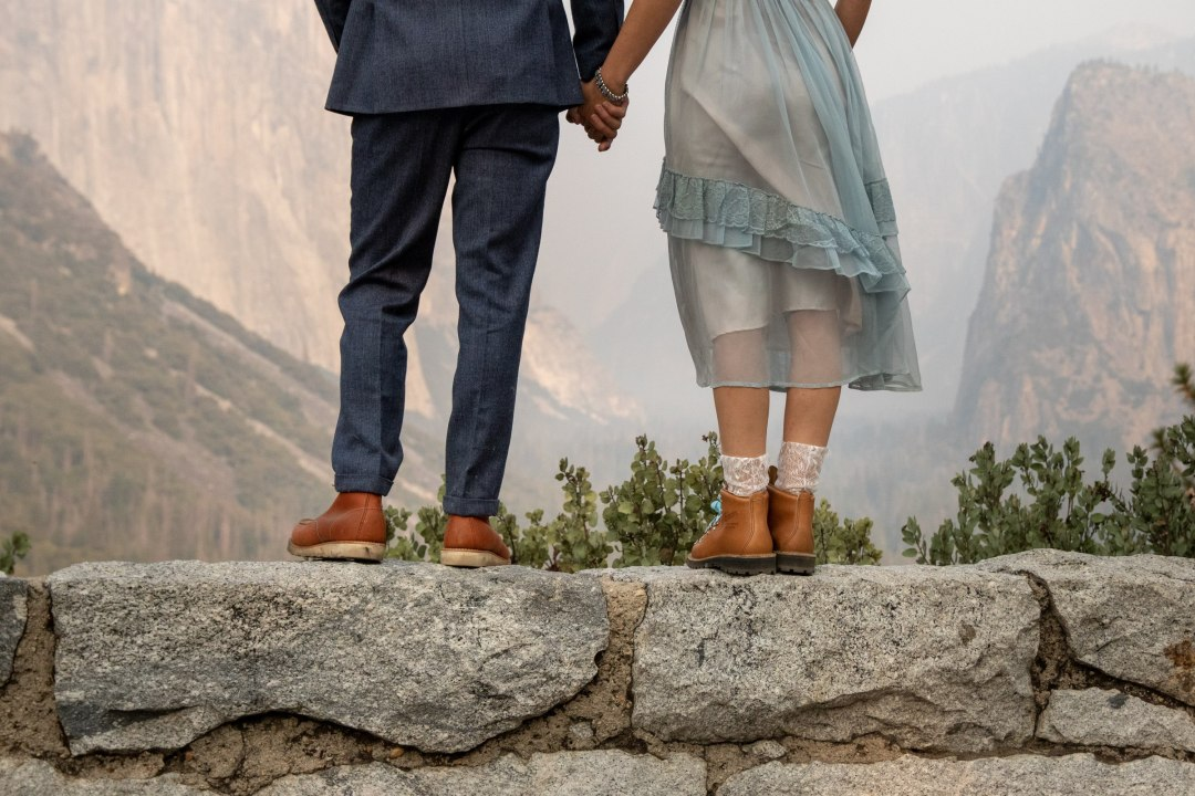 All boots and Valley Views for this couple.   This couple stands on a ledge and looks over Yosemite Valley