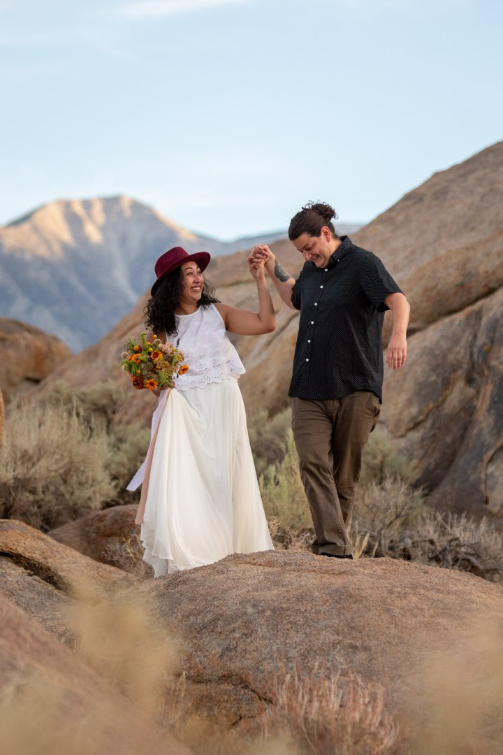 Bride in white dress and red hat with bouquet in her hand is helped over the rocks by her husband.