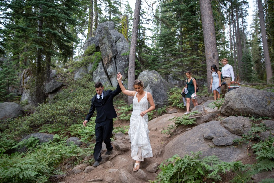 Bride, Groom, and wedding party hiking out to their elopement location.