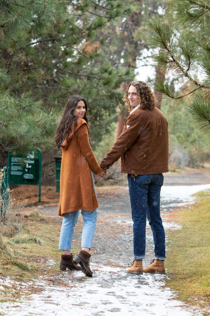 Couple holding hands walk down a snow covered path