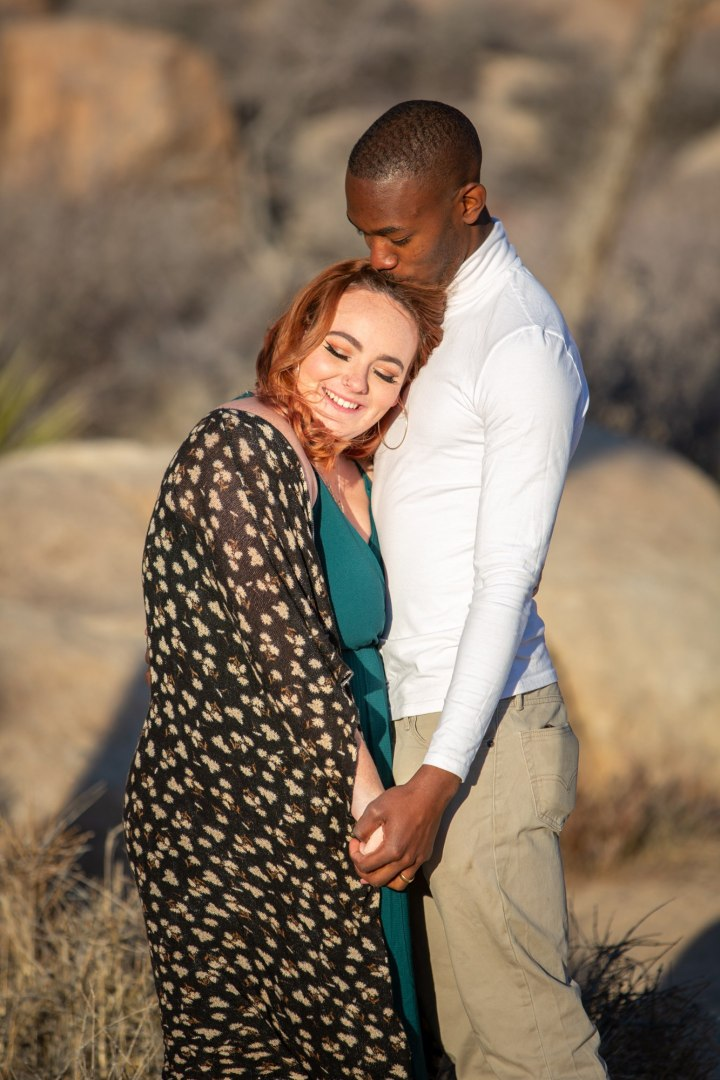 Engaged couple embrace with her head on his shoulder while having a Joshua Tree engagement photo session.
