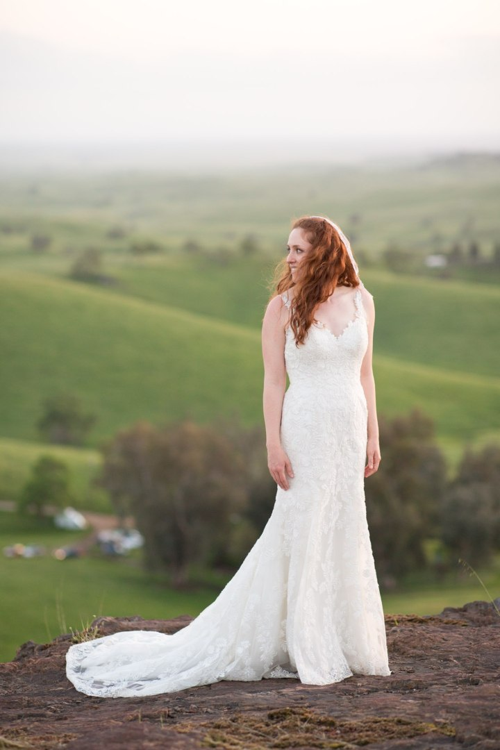 Bride standing with rolling green hills behind.