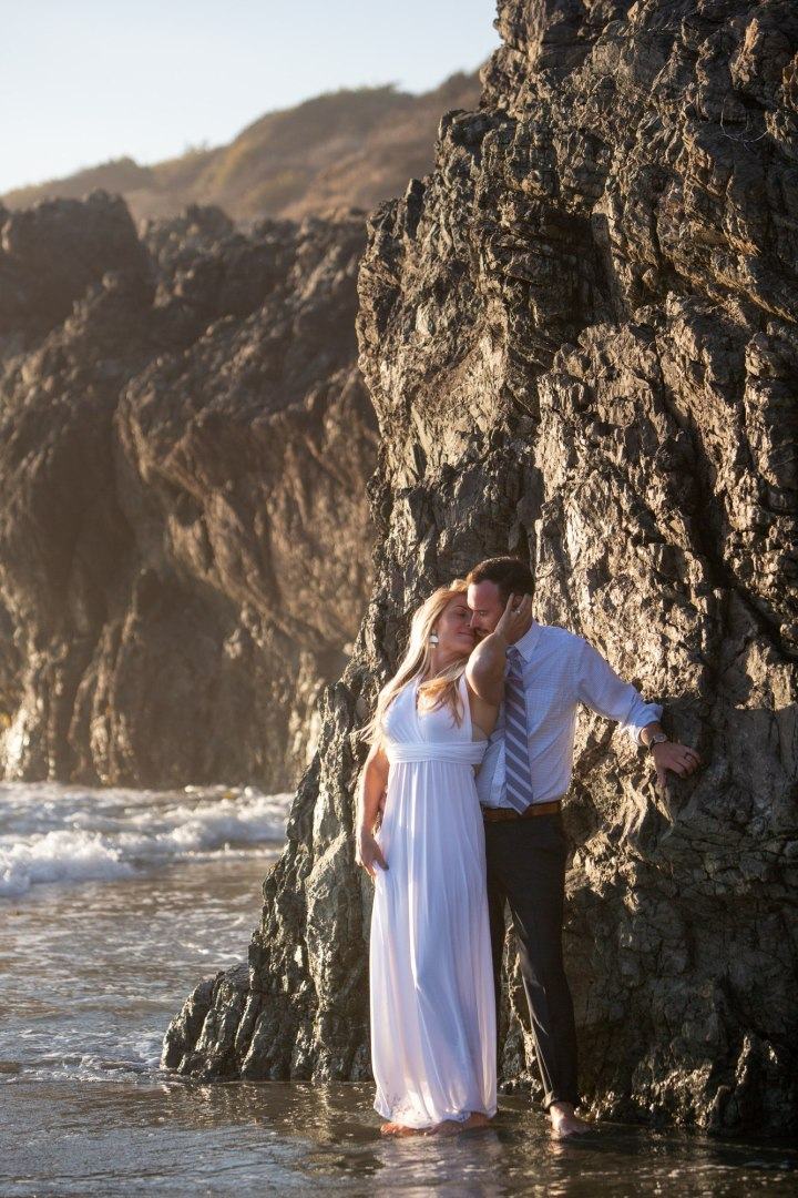 After saying their wedding vows, a couple cuddles up against a rock in Big Sur for a steamy moment.