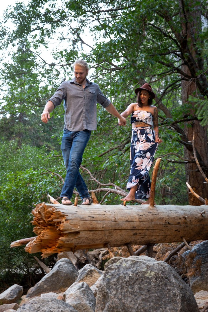 Jon & Tori walking out on a fallen tree during a Yosemite adventure session.