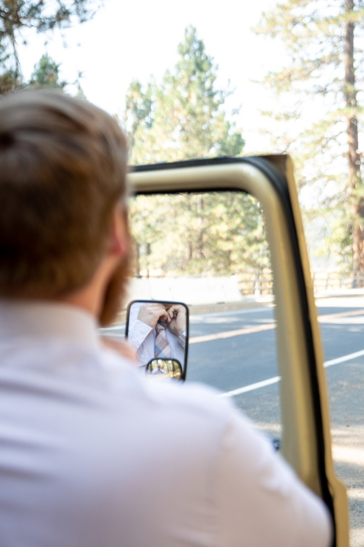 Groom checks himself in the mirror to put his tie on before his Yosemite elopement.