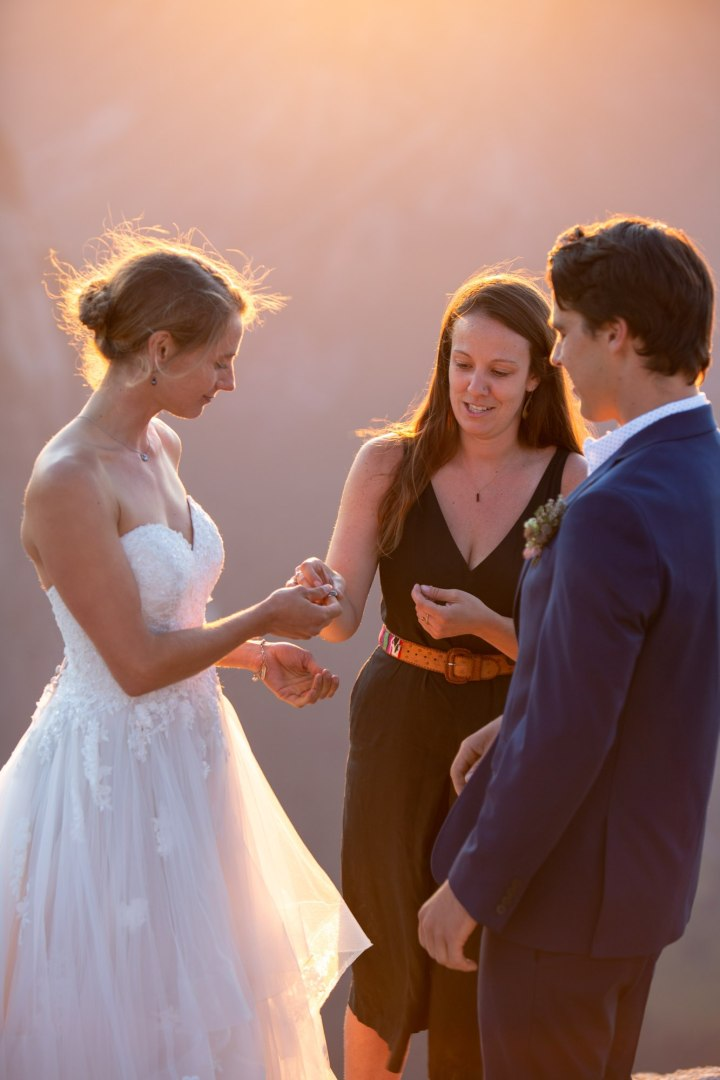 Officiant hands bride rings while groom watches